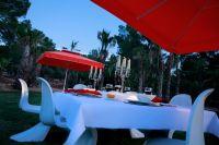 Sonnenschirm-Primus-Riviera-von-Caravita-in-rot-mit-angesetztem-Volant-und-Winddach-auf-Terrasse-00